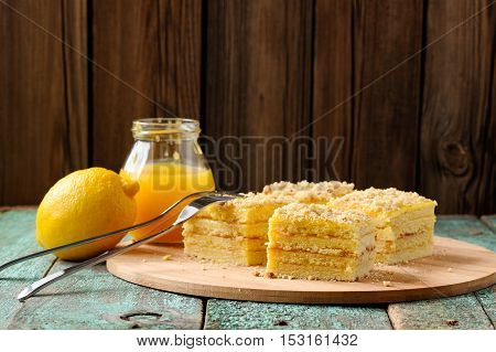 Homemade yummy lemon cake with lemon curd on shabby wooden background with copyspace