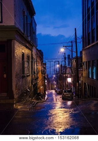 Quebec City, Canada - July 27, 2014: Dark alley way at night in downtown during blue hour with lamps