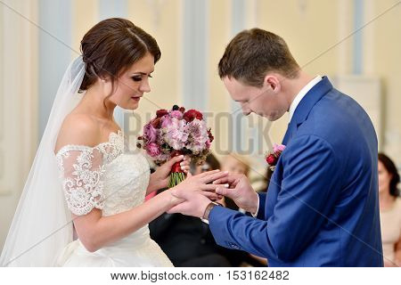 Beauty bride and handsome groom are wearing rings each other. Wedding couple on the marriage ceremony. Beautiful model girl in white dress. Man in suit. Female and male portrait. Cute lady and guy