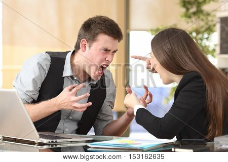 Two furious businesspeople arguing strongly in a desktop with an office background