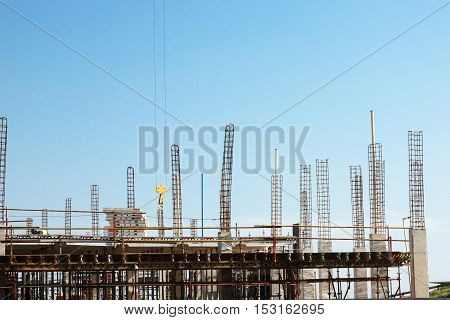 MHLANGA RIDGE DURBAN SOUTH AFRICA - OCTOBER 21 2016: High lift crane and one unknown pearson wokling amongst scaffolding and concrete structures with reinforcing bars extending above work area against blue sky