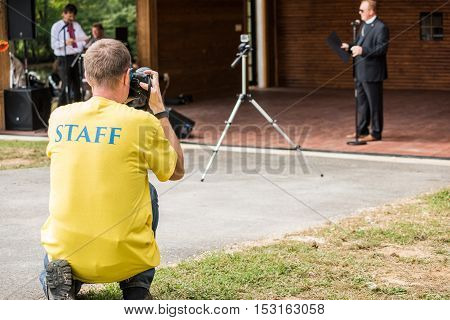 Silver Spring, USA - September 17, 2016: Photographer with blue staff text on yellow shirt at festival taking pictures of priest speaker on stage