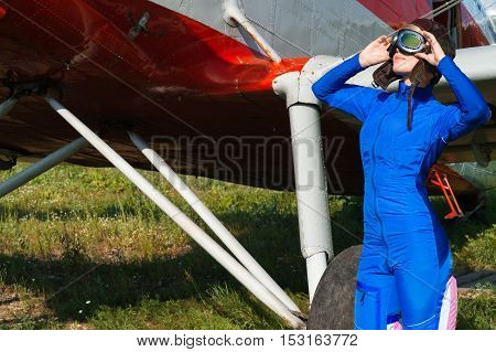 attractive woman pilot on the outdoors with airplane