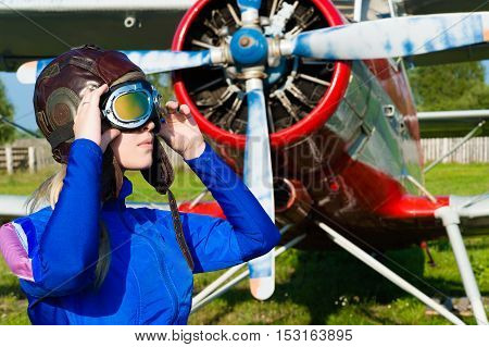 woman pilot in helmet on background of airplane