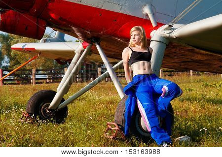 sexy woman pilot enjoying sunlight outdoors with plane