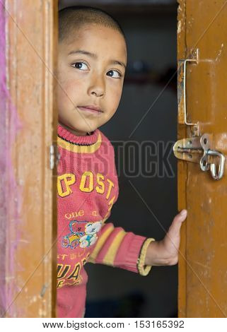 Ladakh, India - August 17, 2015: Young ladakhi girl behind door in Thardot Choeling Nunnery. It is not uncommon for girls in their early teens to run away from home to join a Buddhist nunnery