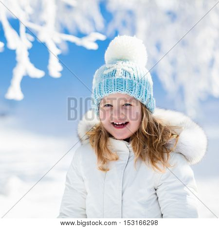 Child in white jacket with fur hood and blue knitted snowflake hat playing in snowy forest on sunny winter day. Toddler kid girl having fun outdoors during Christmas vacation. Kids play in snow.