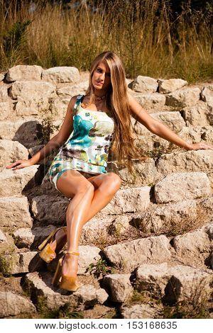 Caucasian long hair model in dress sitting on rocks.