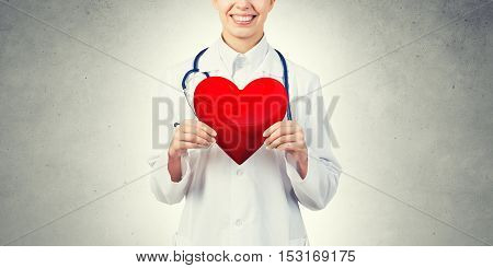 Young woman doctor against gray background holding red heart