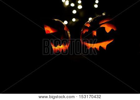 Two Halloween pumpkins with bokeh light on black background