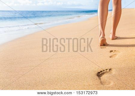 Beach travel - woman relaxing walking on sand beach leaving footprints in the sand. Closeup detail o