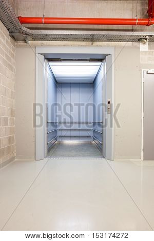 an open elevator on the first floor of an long corridor