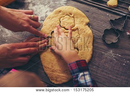 Child cutting gingerbread of metal molds on wooden background