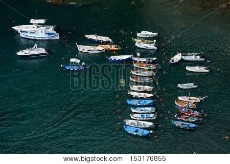 Manarola Italy - September 4 2016: Boats in small port in Vernazza city in Liguria Italy. One of five Cinque Terre cities (unesco world heritage). Unidentified people visible.