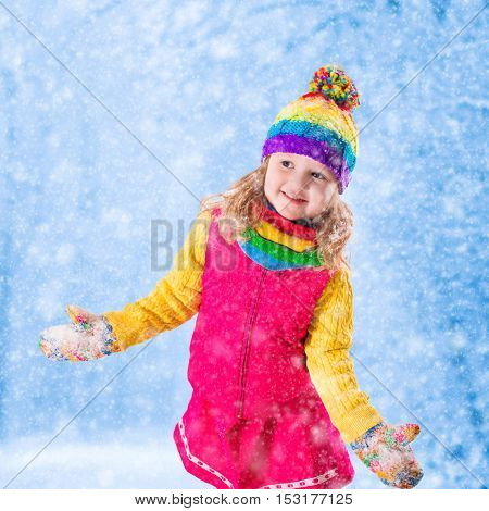 Little girl in pink jacket and colorful knitted hat catching snowflakes in winter park. Kids play outdoor in snowy forest. Children catch snow flakes. Toddler kid playing outside in snow storm.