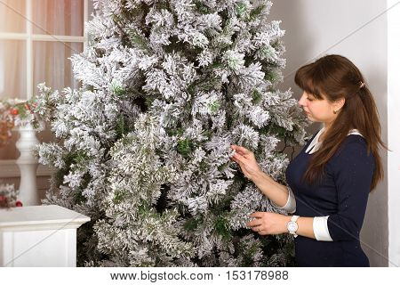 Attractive young girl decorates a Christmas tree in anticipation of New year. Waiting for a miracle in light-colored interiors with snowy pine