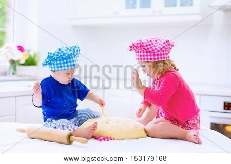 Kids baking. Two children cooking. Little girl and baby boy cook and bake in a white kitchen with modern oven. Brother and sister in chef hats making a pie for dinner.