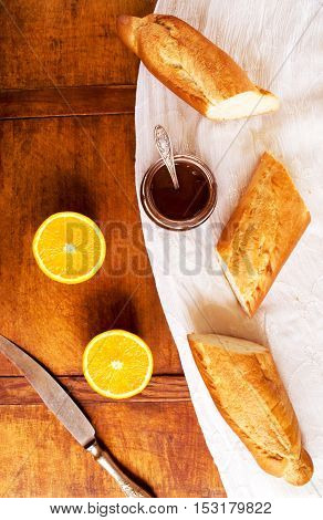 Light breakfast with fresh baguette, chocolate, and oranges on a kitchen table