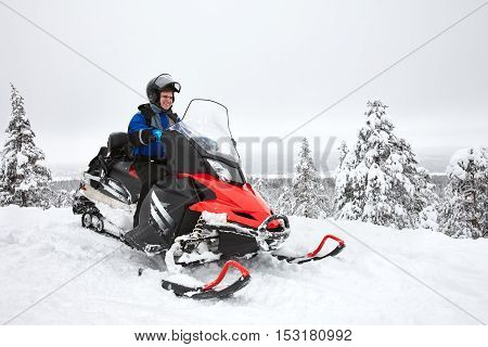 Happy smiling man driving snowmobile in Finnish Lapland