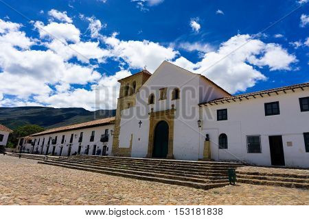 VILLA DE LEYVA COLOMBIA - APRIL 29: Church and shops on the Plaza Mayor in Villa de Leyva Colombia on April 29 2016