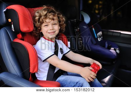 curly smiling baby in the car seat. Red car seat.