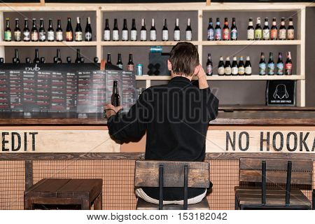 Lonely man in black shirt sitting with his back to the camera at the bar holding a bottle of beer