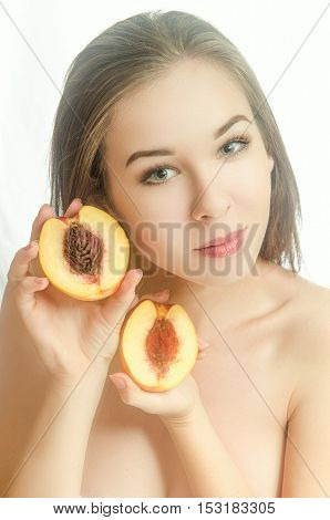 Beautiful girl with two peach halves in her hands on white background. Horizontal photo. Front view