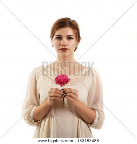 A young woman in a white dress holding a flower