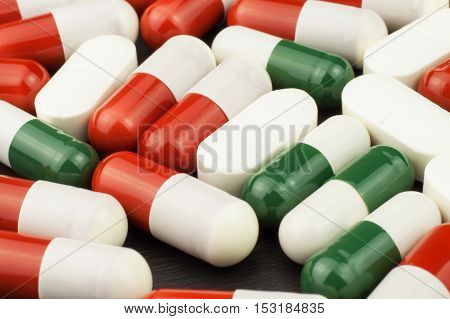 Detailed view of multicolored pills. Pharmaceutical industry. Colorful pills on black background