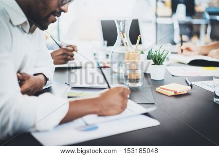 Closeup of dark skinned coworker wearing glasses and working in modern office.African american man in white shirt making notes on the document.Horizontal, blurred background