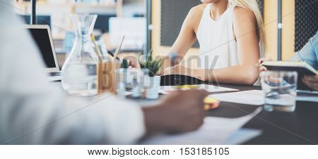 Group of young coworkers working together on modern business project.Woman making notes at the table.Horizontal wide , blurred background