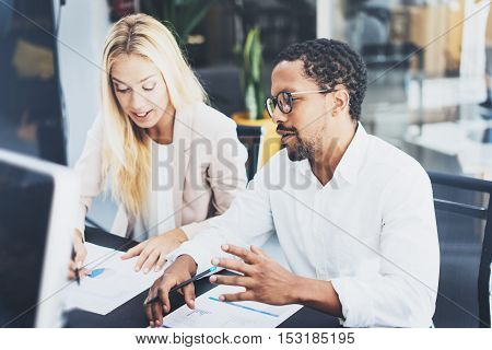Two young coworkers working together in a modern office.Man wearing glasses and discussing with young woman new project.Horizontal, blurred background.