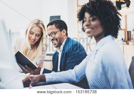 Three young coworkers working together in a modern office.Man wearing glasses and discussing with colleague new project.Horizontal, blurred background.