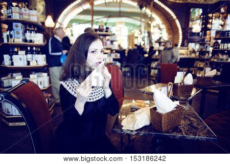 young elegant brunette rich woman in cafe drinking coffee, luxury vintage interior