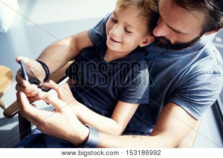 Closeup of young boy sitting with father and using smartphone in modern sunny place. Horizontal, blurred background