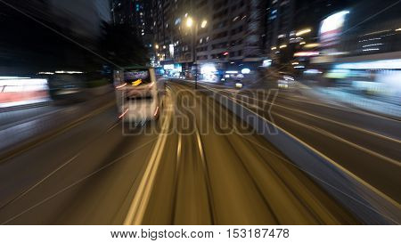 Traveling through the night city by double-decker tram. View to the rails and transport on the road. Shot in motion, Hong Kong