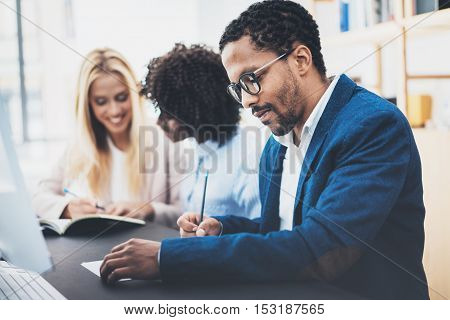 Three young coworkers working together in a modern office.Man wearing glasses, jacket and making notes in a document.Horizontal, blurred background.