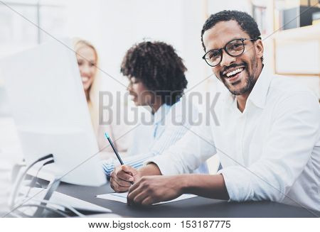 Dark skinned entrepreneur wearing glasses, working in modern office.African american man in white shirt smiling at the camera.Horizontal, blurred background.