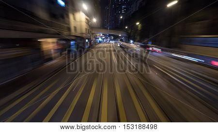 View to the night road from moving tram in Hong Kong. Shot in motion