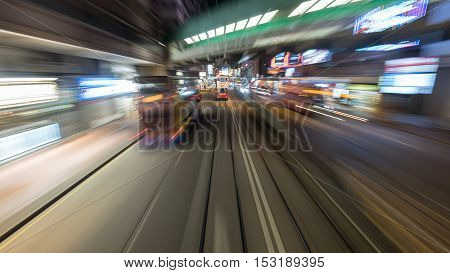 Traveling through night Hong Kong by double-decker tram. View to road with moving bus and rails with another tram. Shot in motion