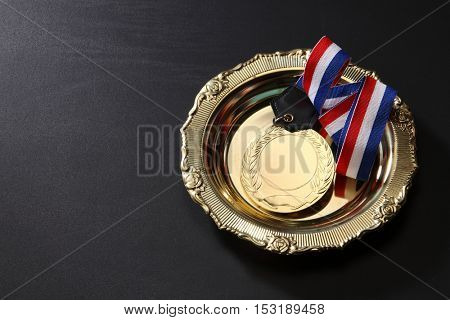 golden medal in a golden tray