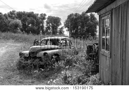 Old abandoned rusty car in autumn. Black and white photography