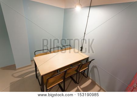 TBILISI, GEORGIA - OCT 8, 2016: Prison style room with wooden table and chairs in a minimalistic design hostel in 8 October, 2016. The annual number of tourists in Georgia reached 2300000 people