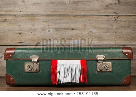 Closed suitcase with a Christmas scarf on a wooden background old surface.