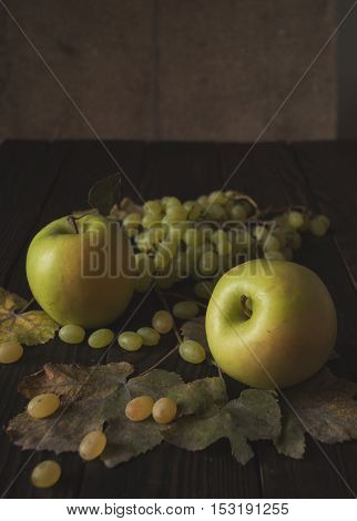Bunch of white grapes, apples and dry leaves on the dark wooden surface