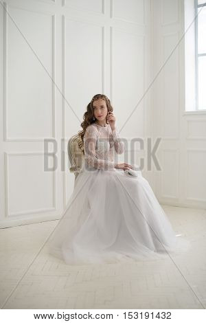 Beautiful young bride sitting on a chair in white room with handbag.