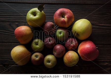 Group of colored apples of different sizes on a wooden surface