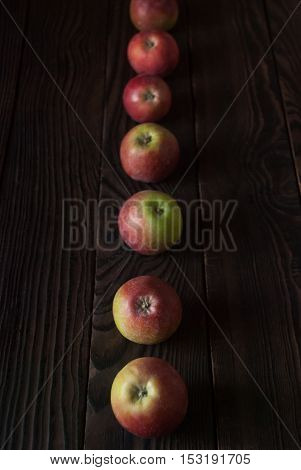 Row of several red apples on a wooden surface