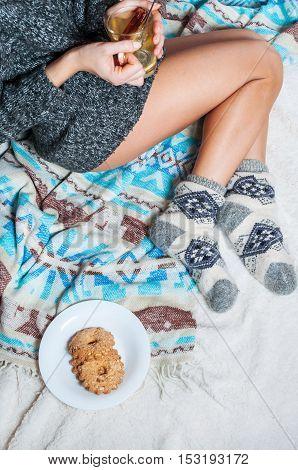 Long female feet in warm woolen socks with cup of tea.