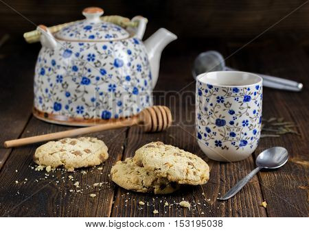 Morning tea with sweet biscuits and teapot behind.